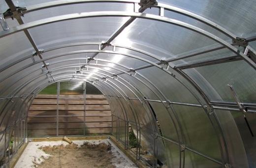 На фото представлен пример теплицы из труб, выполненной в виде арки